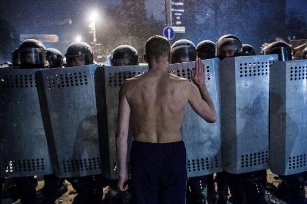 Участник акции протеста разговаривает с сотрудниками спецподразделения милиции Беркут на улице Грушевского в Киеве