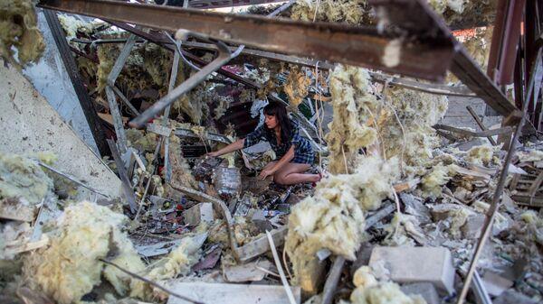 Девушка разбирает завалы в продуктовом магазине, который был разрушен прямым попаданием мины