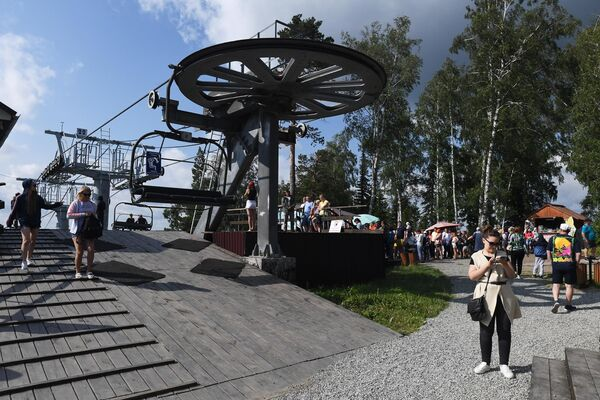 Отдыхающие на верхней станции подъемника на территории всесезонного курорта Манжерок в Республике Алтай