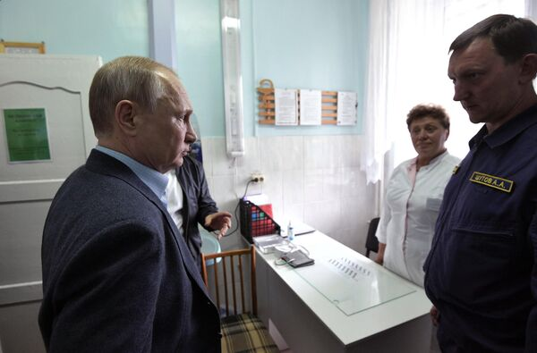 Президент РФ Владимир Путин во время осмотра медицинского кабинета в пункте размещения пострадавшего в результате наводнения населения. 19 июля 2019