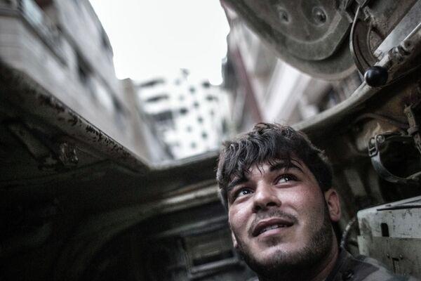 Военнослужащий правительственных войск внутри бронетранспортера во время столкновений с боевиками в центре Хомса