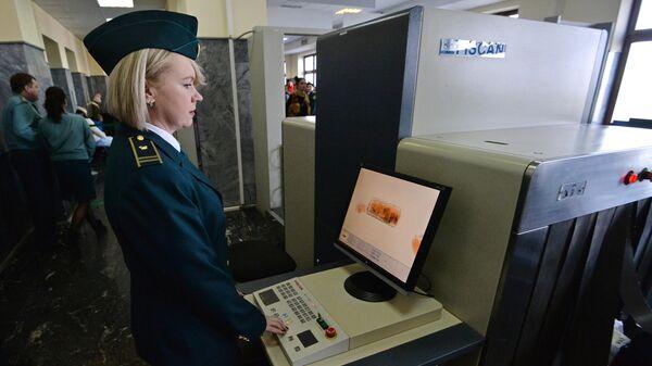 Осмотр багажа с помощью монитора багажного сканера в аэропорту