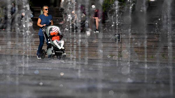 Женщина гуляет с коляской в парке искусств Музеон