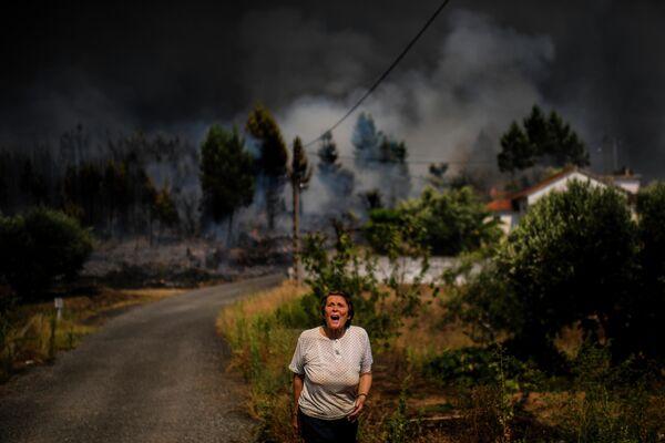 Сельская жительница кричит о помощи, когда лесной пожар приближается к дому в Макао, Португалия