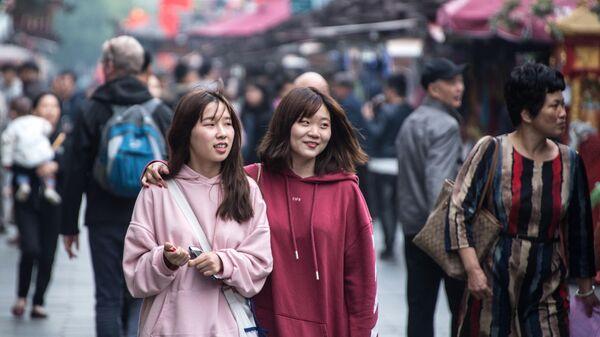 Прохожие на пешеходной улице Хэфан в городе Ханчжоу в КНР