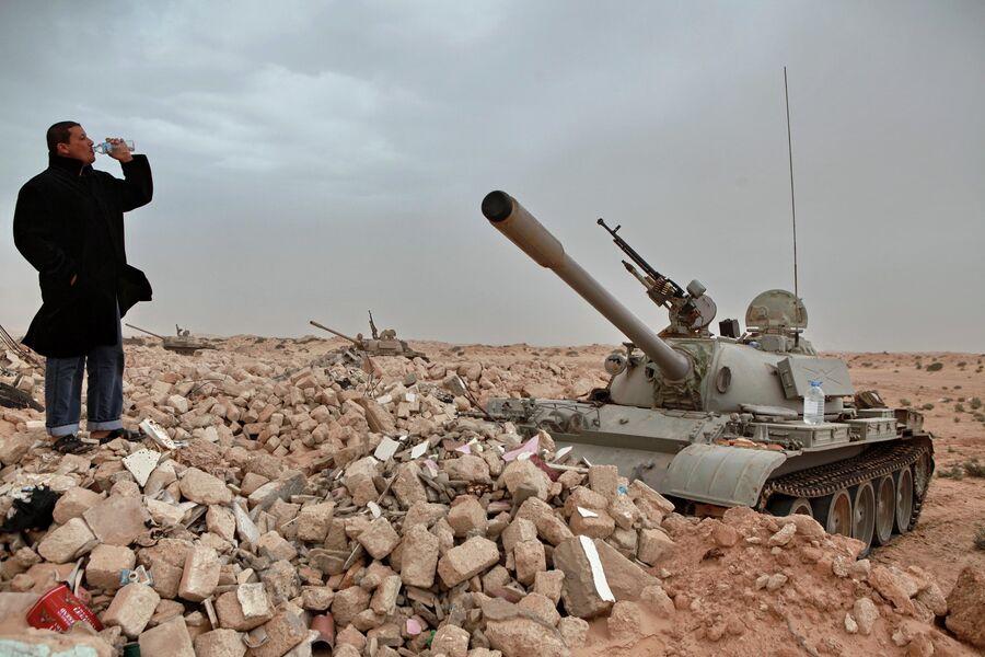 Мужчина у танков ливийской армии, захваченных силами оппозиции, в пустыне под городом Адждабия