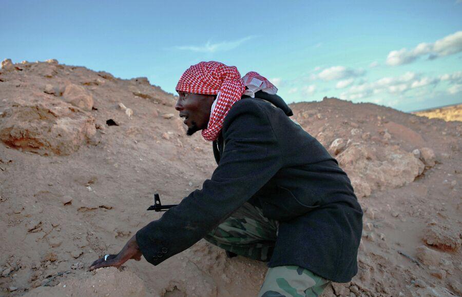 Боец прячется от ракетного обстрела во время боев за город Бин-Джавад