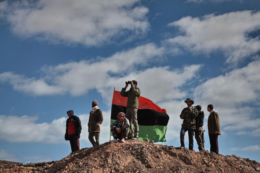 Бойцы оппозиции наблюдают с холма за боем за ходом боев за город Бин-Джавад