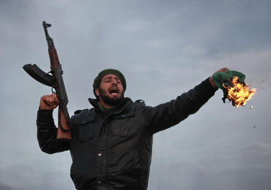 Боец оппозиции сжигает государственный флаг Ливии во время боев за город Рас-эль-Ануф