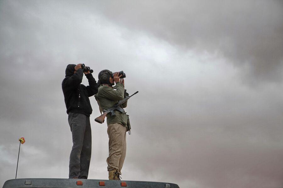 Наблюдатели с биноклями высматривают в небе города Рас-эль-Ануфа истребители войск Муамара Каддафи