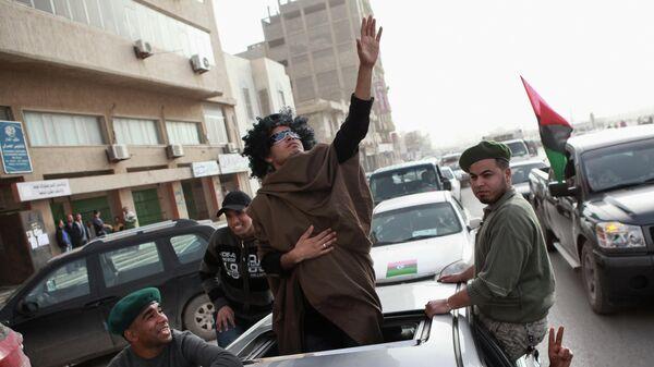 Житель Бенгази изображает Муамара Каддафи на улице города