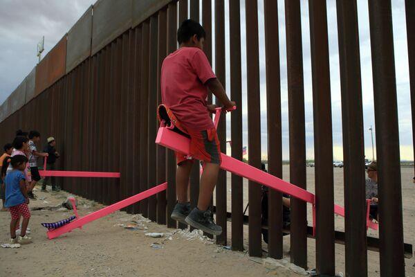 Американские и мексиканские дети качаются на качелях на границе между Мексикой и США