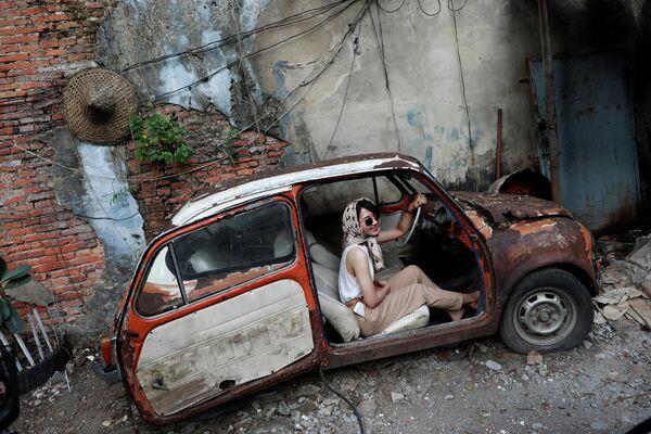 Девушка фотографируется в автомобиле на улице Бангкока