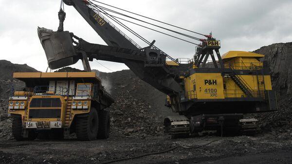 Погрузка породы и угля в карьерные самосвалы на каменноугольном разрезе компании Кузбассразрезуголь