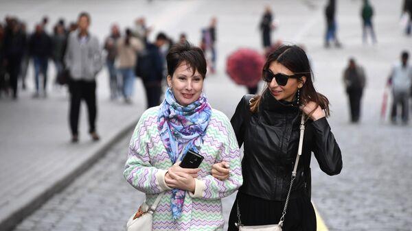 Жители Москвы, одетые в теплые пальто, на Васильевском спуске. 5 августа 2019