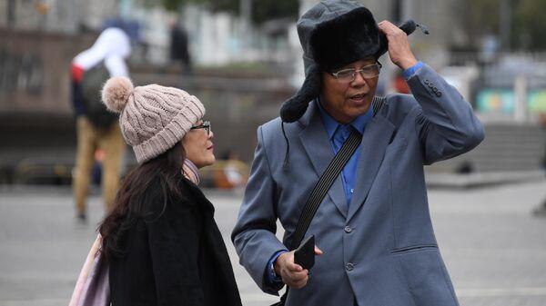 Иностранные туристы, одевают теплые головные уборы, на Манежной площади