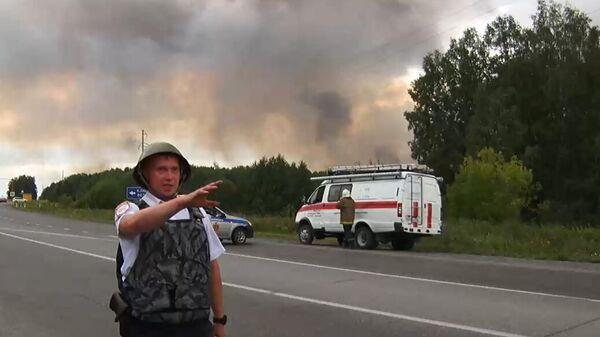 Сотрудник полиции в районе воинской части под Ачинском, где произошли пожар и взрывы на складе хранения артиллерийских боеприпасов. Стоп-кадр с видео