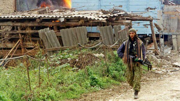 Военнослужащий МВД Дагестана ищет оставшихся исламских боевиков в дагестанском селе Карамахи. 16 сентября 1999 года
