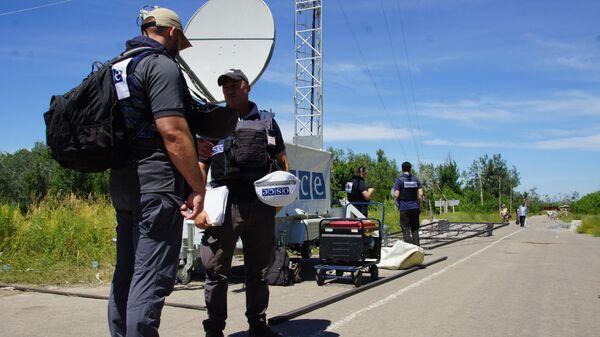 Представители ОБСЕ, прибывшие для наблюдения за первым этапом отвода украинских подразделений, в районе пропускного пункта Станица Луганская