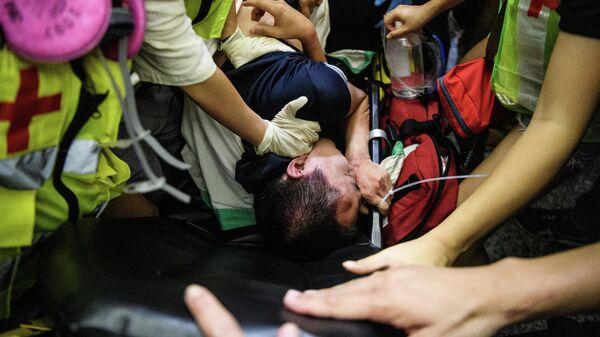 Мужчина окруженный и раненый демонстрантами в международном аэропорту Гонконга, подозревавшими его в том, что он является сотрудником полиции континентальной части Китая. 14 августа 2019