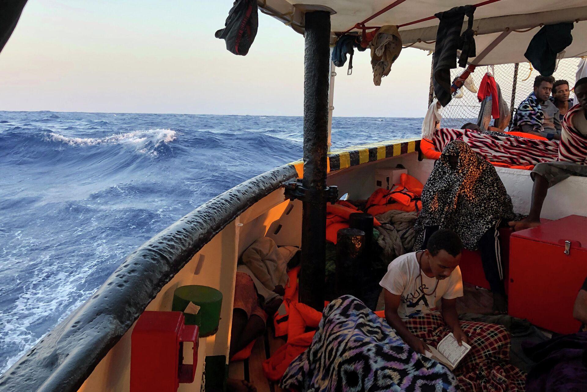 Мигрант читает Коран на борту судна испанских спасателей Open Arms   - РИА Новости, 1920, 13.11.2020
