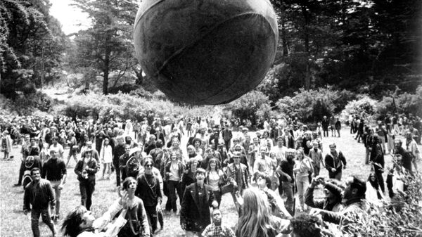 Хиппи запускают воздушный шар с изображением глобуса во время Лета любви в Сан-Франциско. Июнь 1967 года