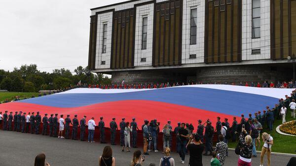 Участники флешмоба развернули государственный флаг Российской Федерации на площади Парка Победы на Поклонной горе в рамках празднования Дня государственного флага России