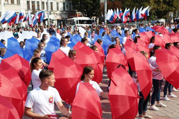 Участники мероприятий составили из зонтов российский триколор в рамках празднования Дня государственного флага Российской Федерации в центре Симферополя