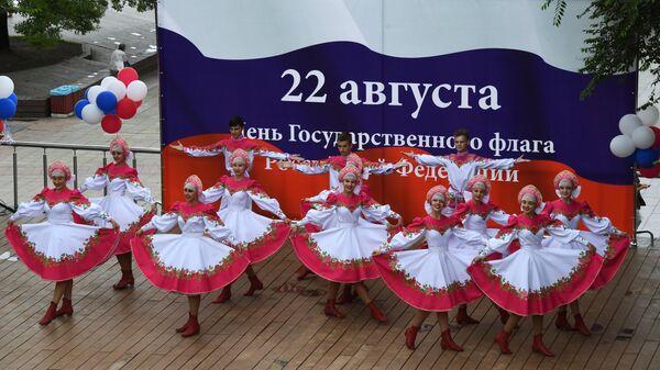 Выступление артистов на праздничном концерте, посвященном Дню государственного флага Российской Федерации, на набережной Спортивной гавани во Владивостоке