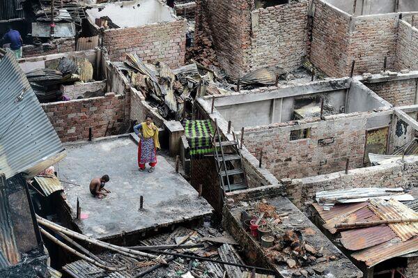 Ребенок играет на крыше сгоревшего дома в трущобах Дакки, Бангладеш