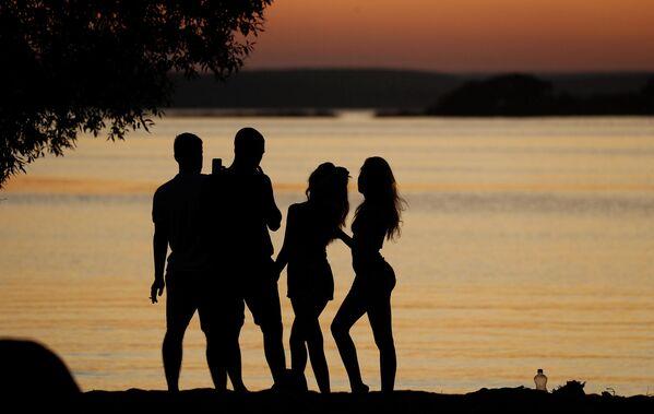Молодые люди смотрят закат на озере около Минска, Белоруссия