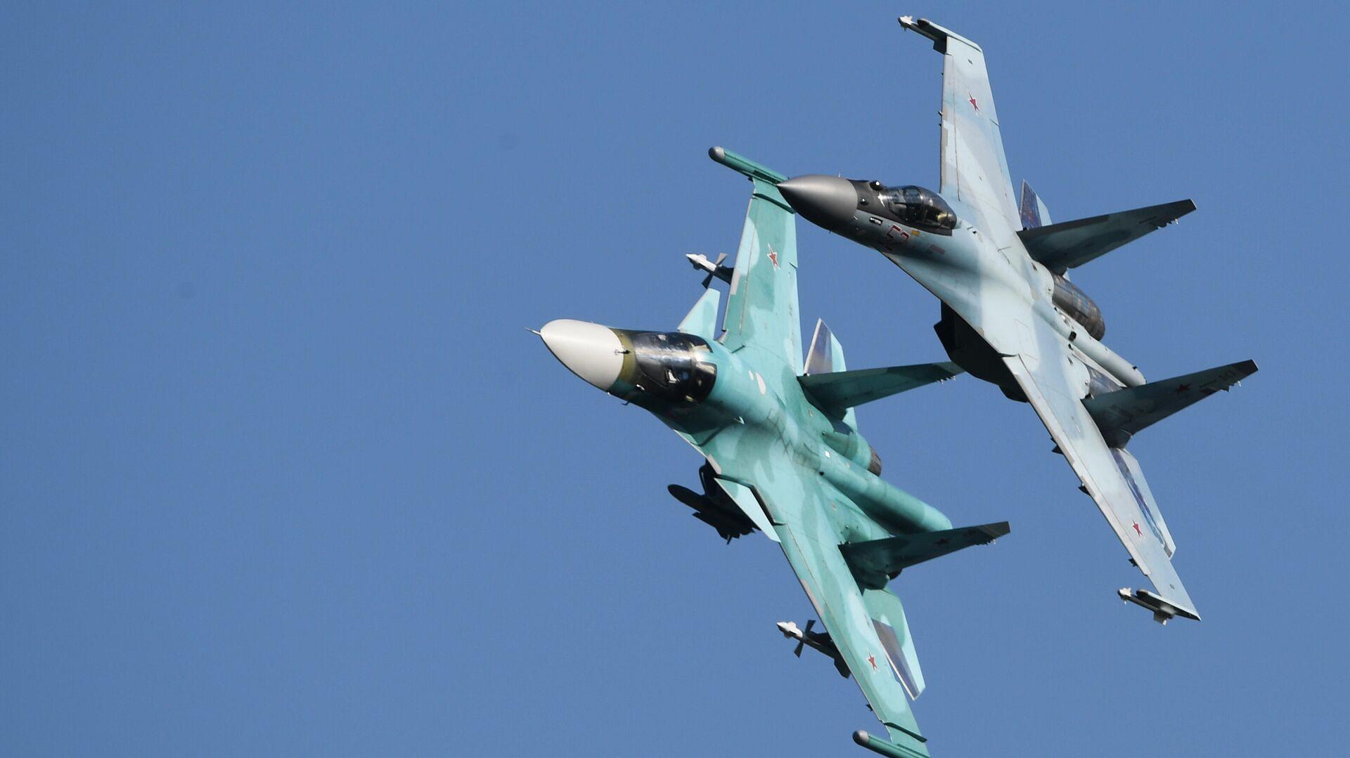 Российские многоцелевые истребители Су-35С (справа) и Су-34 выполняют полет на Международном авиационно-космическом салоне МАКС-2019 - РИА Новости, 1920, 09.04.2021