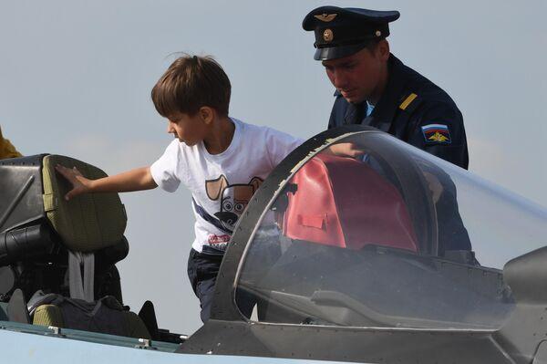 Юный посетитель садится в кабину самолета на Международном авиационно-космическом салоне МАКС-2019 в подмосковном Жуковском
