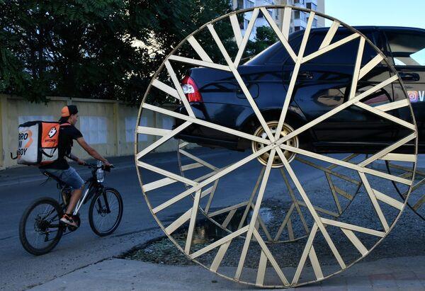 Автомобиль LADA Priora с установленными двухметровыми колесами, стилизованными под колеса кареты, на одной из улиц Краснодара