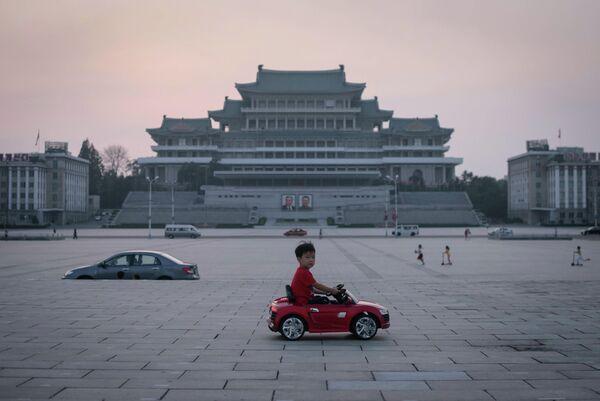 Мальчик на электрическом игрушечном автомобиле на площади имени Ким Ир Сена в Пхеньяне