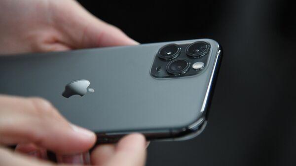 Новый смартфон компании Apple в руках покупателя в магазине re:Store на Тверской улице в Москве