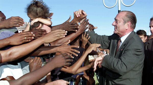 Президент Франции Жак Ширак обменивается рукопожатиями с местными жителями по прибытии в аэропорт им. Памандзи на Майотте. 19 мая 2001 года