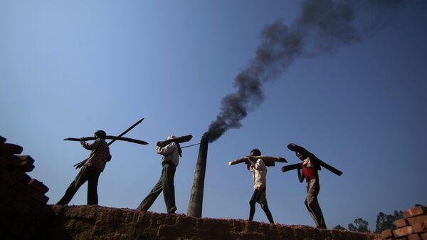 Рабочие на кирпичном заводе на окраине Джамму в Индии