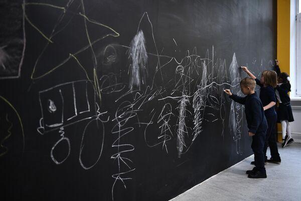 Дети рисуют на меловой доске в холле ГБОУ Школа №444