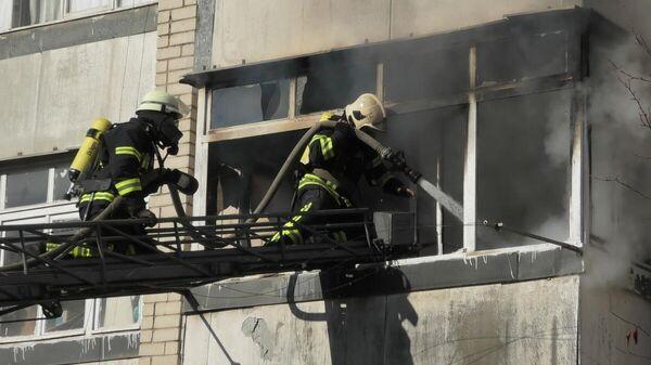 Сотрудники МЧС во время ликвидации пожара на лоджии жилого дома