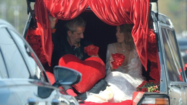 Режиссер Константин Богомолов и телеведущая Ксения Собчак едут в свадебной машине в Москве