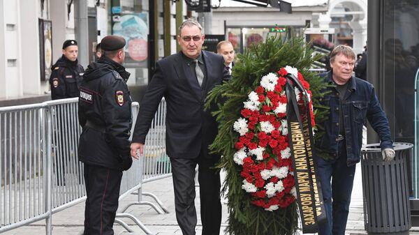 Мужчины с венком у здания театра Ленком в Москве, где проходит церемония прощания с режиссером Марком Захаровым