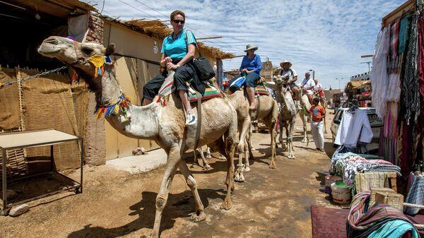 Туристы на верблюдах в деревне Гарб-Сахель в районе Асуана в Египте