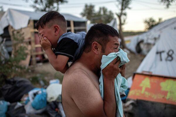 Мигранты после применения полицией слезоточивого газа во время беспорядков в лагере беженцев Мориа на греческом острове Лесбос