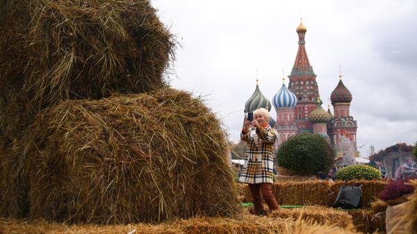 Посетительница фестиваля Золотая осень фотографирует стог сена на Красной площади
