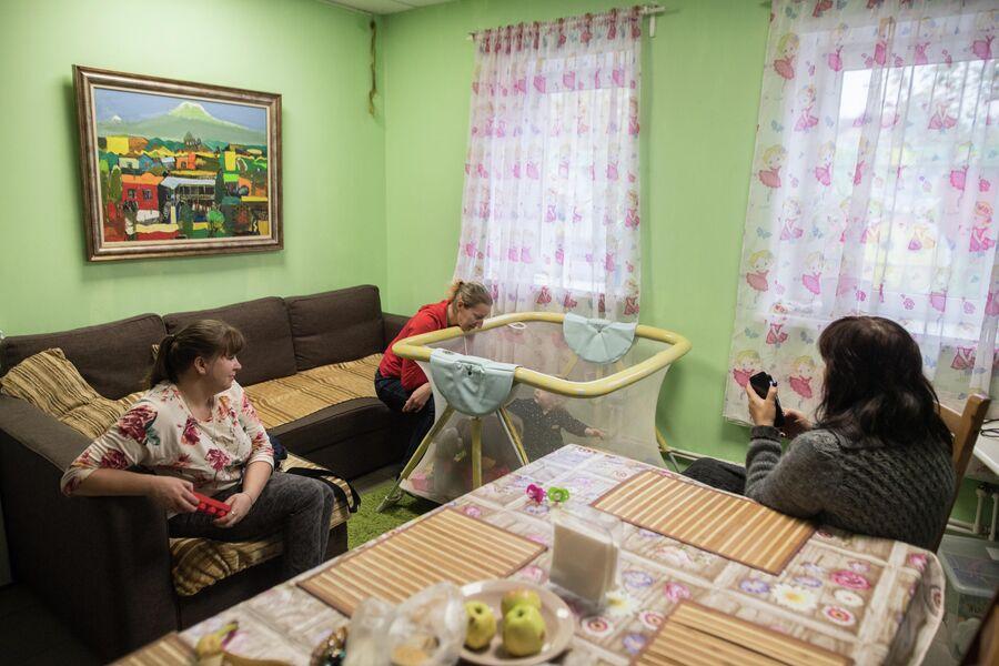 Марина (слева), Алена (справа) и Ирина смотрят, как Наташа играет в манеже