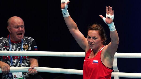 Саадат Далгатова (Россия), победившая в поединке отборочного этапа в весовой категории до 69 кг против Надин Апетц (Германия) на чемпионате мира по боксу AIBA среди женщин в Улан-Удэ. Слева -главный тренер женской сборной России по боксу Иван Шидловский.