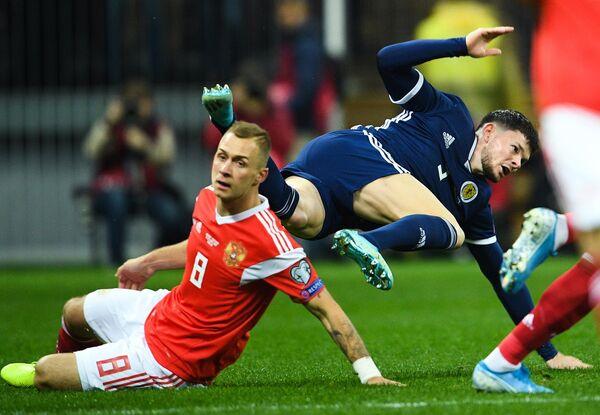 Футболисты сборной России Дмитрий Баринов и сборной Шотландии Эндрю Робертсон (справа)