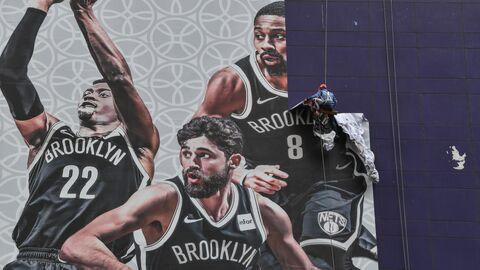 Рабочий снимает рекламный баннер перед матчем Бруклин Нетс – Лос-Анджелес Лейкерс в Шанхае