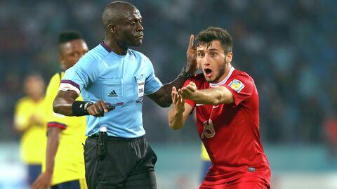 Футболист молодежной сборной Турции Дженк Шахин спорит с судьей